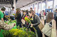 Visitors pick up their free flowers at the UrbanStems booth at the TechDay New York event on Thursday, April 23, 2015. Thousands attended to seek jobs with the startups and to network with their peers. TechDay bills itself as the world's largest startup event with over 300 exhibitors. (© Richard B. Levine)