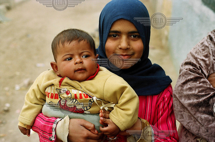 A woman with a child wait outside a mobile health clinic in the impoverished Cairo district of Manshiayt Nasr. The clinic, part of a UNFPA funded project, provides free HIV testing and education and information about HIV/AIDS.