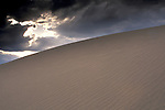 Spring storm clouds and wind patterns in sand dunes at sunset, Stovepipe Wells, Death Valley National Park, California