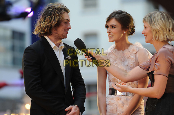 Aaron Taylor-Johnson, Keira Knightley & Edith Bowman.The World Premiere of 'Anna Karenina', The Odeon Leicester Square, London, England..4th September 2012.half length peach pink white sheer fluffy ruffle dress silver belt stubble facial hair black suit sheer side profile microphone interview .CAP/CAS.©Bob Cass/Capital Pictures.