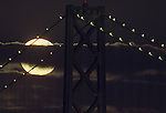 A blue moon rises near the Oakland Bay Bridge in San Francisco California.