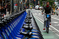 New York, USA. 28 May 2014. A man rides a Citi bike next to a rental location during the one year anniversary in New York. Photo by Eduardo Munoz Alvarez/VIEWpress