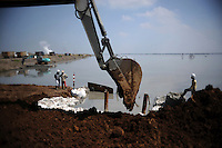 Diggers continue building up the earthen dam walls that are stopping the mud flow from expanding. Since May 2006, more than 10,000 people in the Porong subdistrict of Sidoarjo have been displaced by hot mud flowing from a natural gas well that was being drilled by the oil company Lapindo Brantas. The torrent of mud - up to 125,000 cubic metres per day - continued to flow three years later.