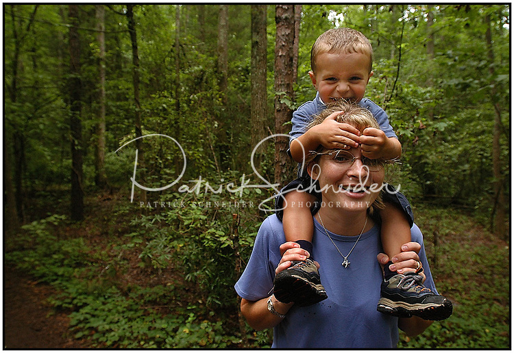 A young boy holds onto his mother's head while they take a walk through the woods at the Carolina Raptor Center. Model released image, can be used for multiple purposes.