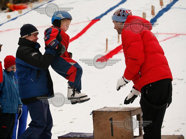 Njål Mønsdal  is helpet to the podium after winning his age group in Jardarkollen ski jump arena.