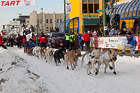 Musher Paul Gebhardt and Iditarider Julieanne Brackin.leave the 2011 Iditarod ceremonial start line in downtown Anchorage, Alaska