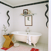 In the bathroom the curly black horns displayed on the walls are South African Kudu, the framed drawing is a work by Robbie Scott-Duff and the geometric wooden stool is a Nicky Haslam design