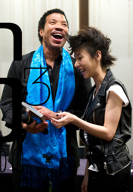 HONG KONG, CHINA - SEPTEMBER 27:  US singer/songwriter Lionel Richie and Hong Kong singer Vincy Chan laugh during a press conference a day before Richie's special one-night concert, at the W Hotel on September 27, 2010 in Hong Kong.  Photo by Victor Fraile / studioEAST