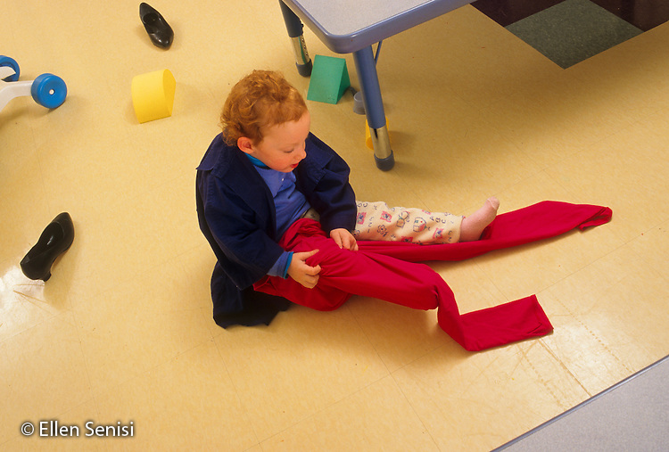 MR / Schenectady, New York. Schenectady Day Nursery (private nonprofit daycare center). Toddler class. Girl (30 months) puts on pants that are too big for her at playtime as she plays dress-up. MR: Rob5. © Ellen B. Senisi