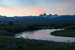 Idaho, Eastern, Teton County, Driggs, Tetonia. A sweeping bend in the Teton River in spring with the Teton Range and pink morning clouds at dawn.