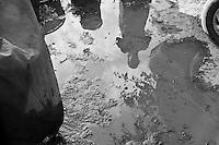Basilicata 2010 - Vita rurale - Contadina in trasparenza nell'acqua usata per lavare gli ortaggi.