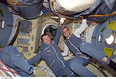 """Two Soyuz Taxi crewmembers, Flight Engineer Roberto Vittori (left) of the European Space Agency (ESA) and South African space flight participant Mark Shuttleworth, are photographed in the Pirs docking compartment on the International Space Station (ISS). Soyuz Taxi  Commander Yuri Gidzenko, representing Rosaviakosmos, is out of frame. The """"taxi"""" crew arrived at the orbital outpost on April 27, 2002 at 2:56 a.m. (CDT) as the two vehicles flew over Central Asia.<br /> Credit: NASA via CNP"""
