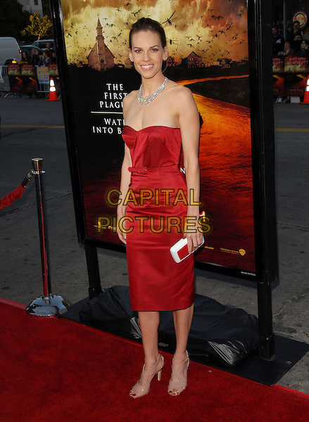 """HILARY SWANK .The Warner Brothers' Pictures L.A. Premiere of """"The Reaping"""" held at The Mann Village Theatre in Westwood, California, USA..March 29th, 2007.full length red strapless dress belt diamond necklace white clutch purse .CAP/DVS.©Debbie VanStory/Capital Pictures"""