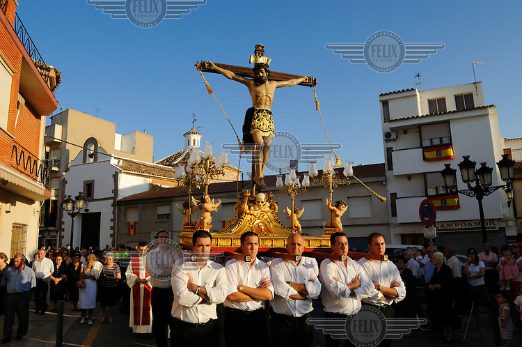 A group of men, known as costaleros, carry a float (paso) bearing a wooden carving of the crucifixion during a Catholic religious procession through the town of Campo de Criptana.