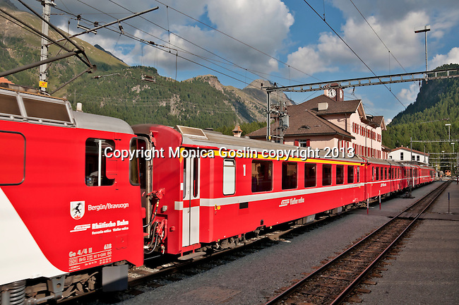 Swiss red Bernina Express trains stop at the Swiss town of Pontresina with a pink train station, on the way to St. Moritz, Switzerland
