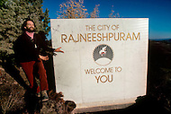 Wasco, Oregon, January 1984:Swami Krishna Deva, Master of the Rajneeshpuram Community, in front of the sign indicating the entrance to the town.  Rajneeshpuram, was an intentional community in Wasco County, Oregon, briefly incorporated as a city in the 1980s, which was populated with followers of the spiritual teacher Osho, then known as Bhagwan Shree Rajneesh. The community was developed by turning a ranch from an empty rural property into a city complete with typical urban infrastructure, with population of about 7000 followers.