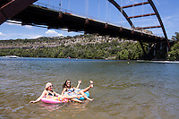 Two beautiful women relax and suntan while floating inner tubes on a popular beach on Lake Austin at the Loop 360 Bridge Park Beach