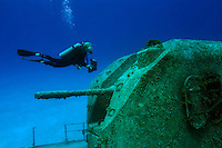 Female diver (MR) with a camera and scuba diving on the wreck of the Captain Keith Tibbetts in Cayman Brac, Cayman Islands.