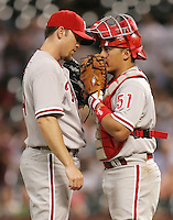 Phiilies pitcher Brad Lidge meets with catcher Carlos Ruiz on Thursday May 22nd at Minute Maid Park in Houston, Texas. Photo by Andrew Woolley / Four Seam Images.