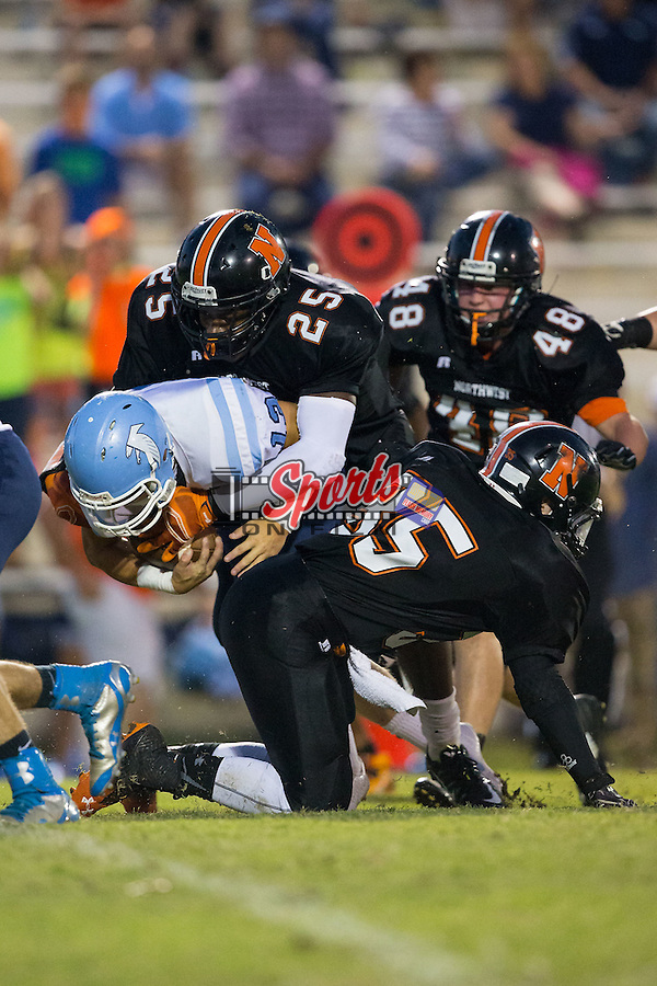 Harrison Baucom (13) of the West Rowan Falcons is tackled by Anthony Caldwell (25) and Cameron Threadgill (35) of the Northwest Cabarrus Trojans during first half action at Trojan Stadium September 19, 2014, in Concord, North Carolina.  The Falcons defeated the Trojans 13-0.  (Brian Westerholt/Sports On Film)