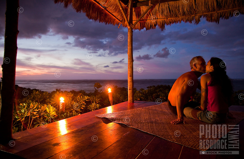 A couple kissing at sunset in their beachfront gazebo