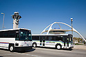 Two buses against blue sky. The LAX (Los Angeles International Airport) shuttle bus is a natural gas vehicle. Los Angeles, California, USA