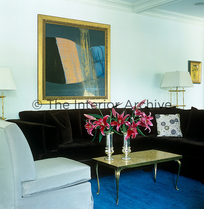 A large abstract gilt-framed painting hangs on the wall of the sitting room above a brown velvet sofa