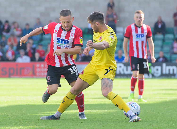 Lincoln City's Jack Payne vies for possession with Fleetwood Town's Wes Burns<br /> <br /> Photographer Chris Vaughan/CameraSport<br /> <br /> The EFL Sky Bet League One - Lincoln City v Fleetwood Town - Saturday 31st August 2019 - Sincil Bank - Lincoln<br /> <br /> World Copyright © 2019 CameraSport. All rights reserved. 43 Linden Ave. Countesthorpe. Leicester. England. LE8 5PG - Tel: +44 (0) 116 277 4147 - admin@camerasport.com - www.camerasport.com