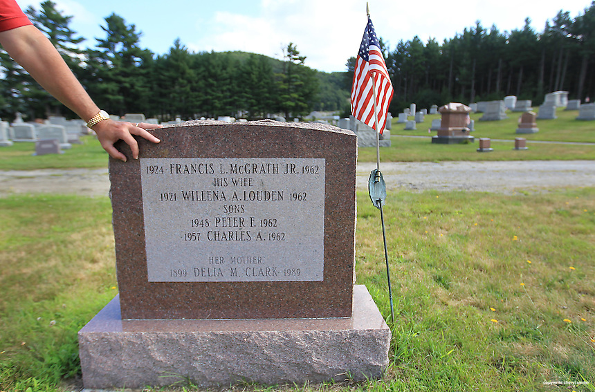 Lieutenant Barry Hunter rests his hand on the McGrath family headstone at Pinegrove Cemetery in Newport, N.H., Friday, Aug. 5, 2011.  It was 37 years ago when John William McGrath, who murdered his parents and two brothers, wandered away from the New Hampshire Hospital, where he was committed when a grand jury declared him insane. Lieutenant Barry Hunter has been looking for McGrath for 27 of those 37 years.  (Cheryl Senter for the Boston Globe)
