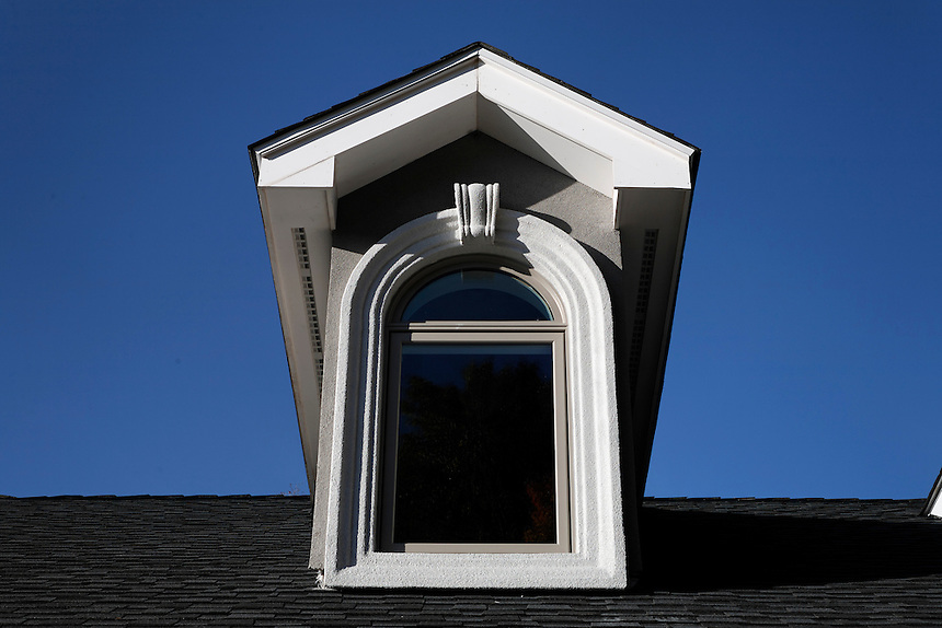 Dormer with arch top window and decorative corbel and stucco.