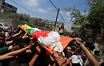 Mourners carry the body of Palestinian Mahmoud al-Ghrabli ,16, who died of wounds he sustained during clashes with Israeli troops, his funeral in Gaza city on July 5, 2018. Photo by Ashraf Amra