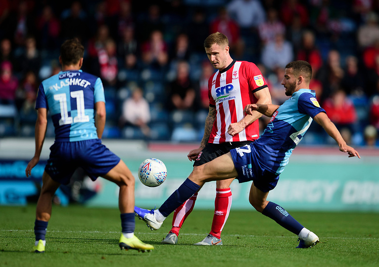 Lincoln City's Michael O'Connor clears under pressure from Wycombe Wanderers' Scott Kashket, left, and Nick Freeman<br /> <br /> Photographer Andrew Vaughan/CameraSport<br /> <br /> The EFL Sky Bet League One - Wycombe Wanderers v Lincoln City - Saturday 7th September 2019 - Adams Park - Wycombe<br /> <br /> World Copyright © 2019 CameraSport. All rights reserved. 43 Linden Ave. Countesthorpe. Leicester. England. LE8 5PG - Tel: +44 (0) 116 277 4147 - admin@camerasport.com - www.camerasport.com