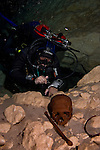 Guillermo de Anda, diving in a cenote filled with Mayan artifacts, inspects sacrificial remains. Near Homum, Yucatan, Mexico.