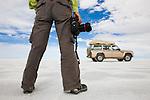 Bolivia, Altiplano, woman holding camera with 4x4 vehicle on Salar de Uyuni, world's largest salt pan
