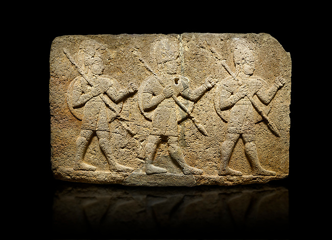 Hittite monumental relief sculpted orthostat stone panel of Herald's Wall Basalt, Karkamıs, (Kargamıs), Carchemish (Karkemish), 900-700 B.C. Anatolian Civilisations Museum, Ankara, Turkey. Military parade. Two helmeted soldiers in short skirts carry the shield on their backs and the spears in their hands. <br /> <br /> Against a black background.