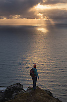Female hiker watches sun over sea from Nonstind mountain peak, Vestvågøy, Lofoten Islands, Norway