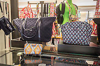 A selection of handbags by Vera Bradley are seen in a department store in New York on Wednesday, June 3, 2015. First quarter sales slumped 17 percent which was the eighth decline in 10 quarters. The company plans a new marketing campaign to attract customers to its other products besides its signature quilted bags.  (© Richard B. Levine)