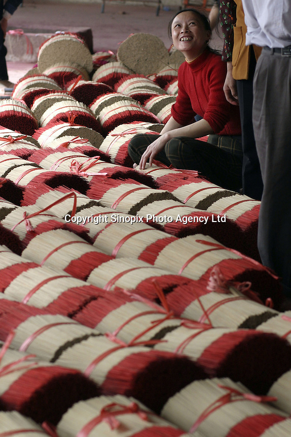 A female worker waits for her turn of the weigh-in at the Meizhengxiang Incense Factory near Xiamen, Fujian Province, China. As religous life increasingly becomes an important part of China, businesses related to religion such as Buddhism and Daoism have flourished. The factories have seen its sales quadruple since its establishment in 1996, reaching euro 5 million in 2003. The factory now employs over 200 workers, mostly migrants from Sichuan and Jiangxi Province..17-MAR-04