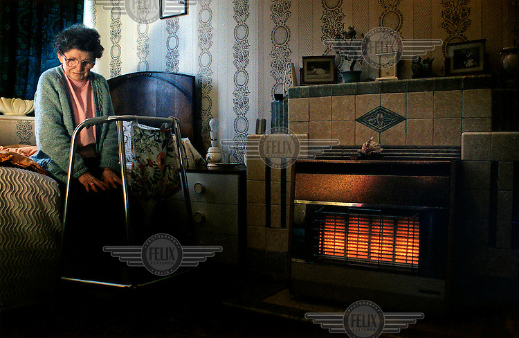 An elderly woman with a Zimmer frame warms herself by an electric heater.