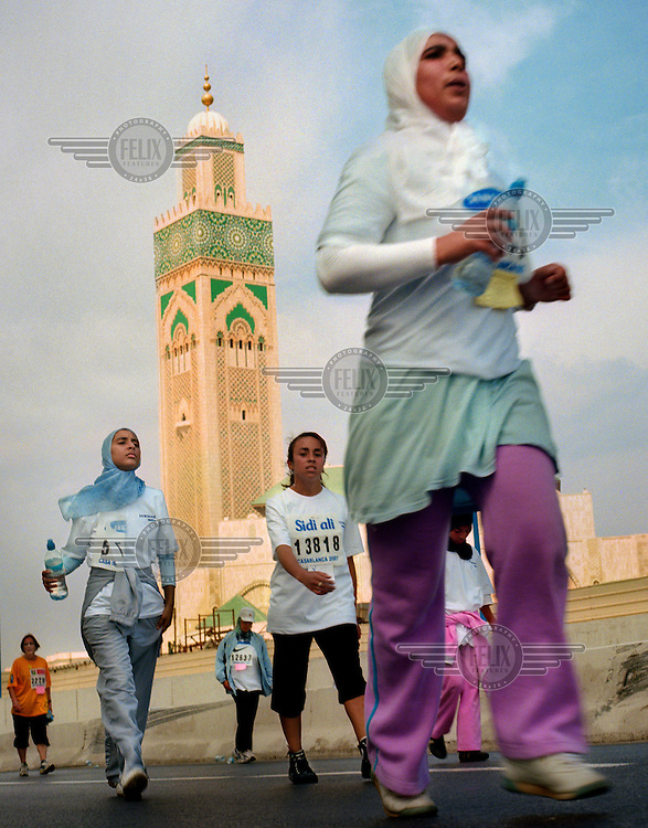Veiled female competitors running past a mosque during a women's race that was organised by the Laureus Courir Pour La Vie (Run For Life) project to promote sports activity among teenage girls. The project is supported by Moroccan athlete Nawal El Moutawakel, who was the first African and the first Muslim woman to win an Olympic gold medal when she won the 400-metre hurdles in 1984.