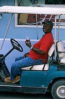 Les Bahamas /Ile d'Eleuthera/Harbour Island/Dunmore Town: bahaméen prenant un verre a bord de sa Golf Cart les voitures de golf sont utilsés sur l'ile comme moyen de transport