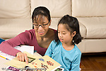 8 year old girl at home doing homework for Chinese language class working with help from mother horizontal
