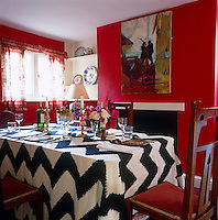 The dining room of Penny Graham's house is arranged with stunning simplicity where a black-and-white herringbone tablecloth sings against poppy-red walls