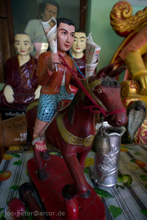 Nat spirit on horse with money attached as offering in shrine at Mount Popa temple area, Myanmar, 2011