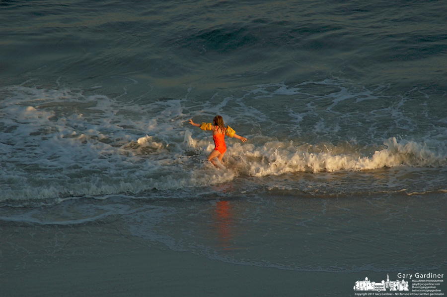 A girls plays in a spray of light at the ocean's edge in the late afternoon in Virginia Beach, Va.