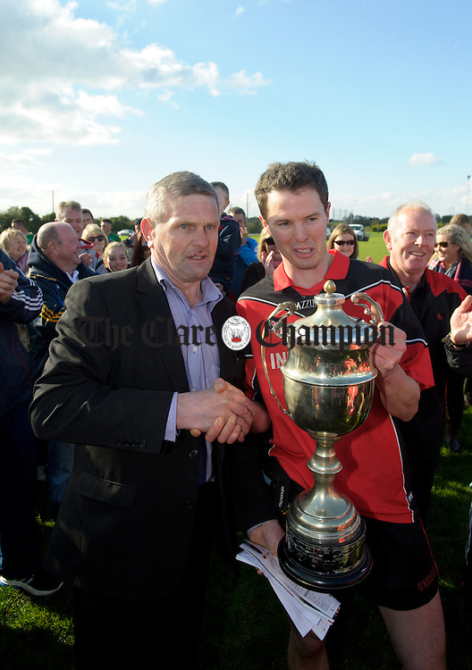 Meelick  captain Kevin Harnett accepts the cup from Clare GAA chairman Joe Cooney following the win over Kilmurry Ibrickane in their Junior A  county final at Gurteen. Photograph by John Kelly.