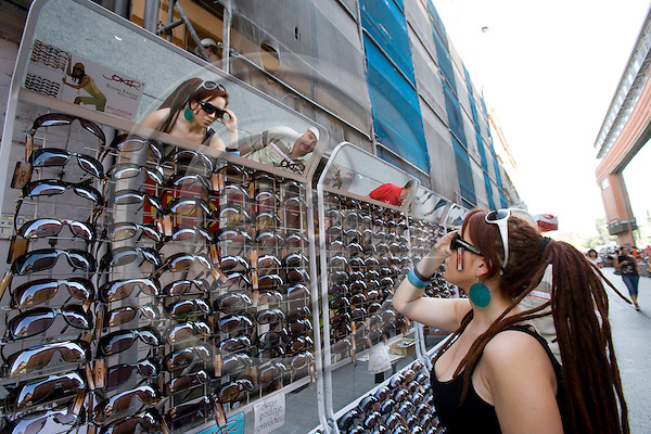 POZNAN - POLAND - 3 JUNE 2008 -- A lady looks in a mirror as she tries sun glasses at a street seller the shopping street. Photo: Erik Luntang/EUP-IMAGES
