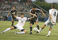 Pablo Hernandez #21 of D.C. United shoots between Jason Hotchkin #11 and Geoff Bloes #4 of the Harrisburg City Islanders during a US Open Cup match at the Maryland Soccerplex on July 21 2010, in Boyds, Maryland. United won 2-0.