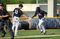 Tampa Yankees manager Pat Osborn (13) congratulates third baseman Miguel Andujar (27) after hitting a home run during a game against the Lakeland Flying Tigers on April 7, 2016 at Henley Field in Lakeland, Florida.  Tampa defeated Lakeland 9-2.  (Mike Janes/Four Seam Images)
