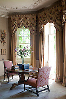 A pedestal table and pair of armchairs furnish the bay window in the drawing room which is dressed with elegant curtains with swagged pelmets